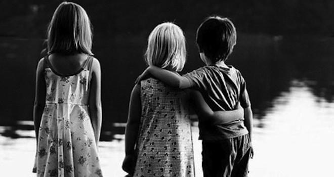 Tres niños mirando a un lago