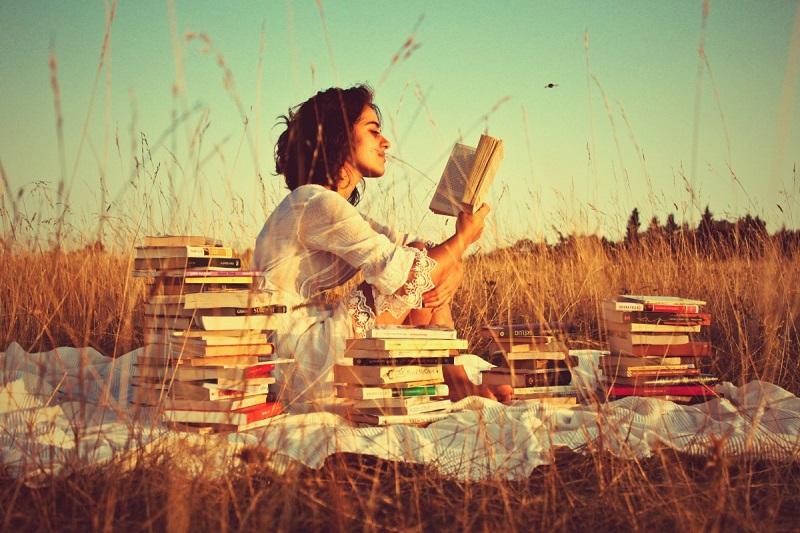 Chica leyendo un libro en el campo
