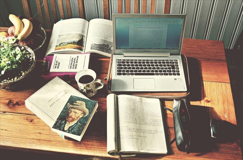 Imagen de libros y ordenador sobre una mesa
